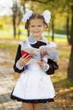 Happy little schoolgirl in autumn park Stock Images
