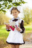 Happy little schoolgirl in autumn park Royalty Free Stock Photos