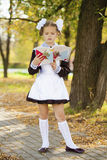 Happy little schoolgirl in autumn park Royalty Free Stock Images