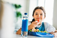 happy little schoolgirl eating lunch stock photos