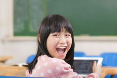 Happy little schoolgirl holding digital tablet Stock Photos