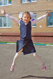 Happy little schoolgirl jumping. Raising his hands up stock images