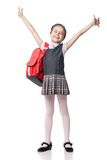 Happy little schoolgirl in uniform standing on Royalty Free Stock Photos