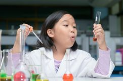 Happy little scientist in lab coat making experiment royalty free stock photos