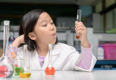 Happy little scientist in lab coat making experiment royalty free stock photography