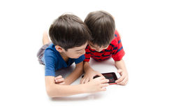 Happy little sibling boy use tablet on white background Royalty Free Stock Photo
