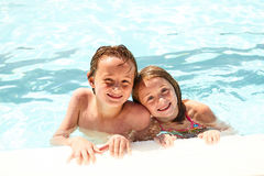 Happy little siblings or friends in swimming pool. Portrait of happy little siblings or friends looking at camera and smiling in swimming pool Stock Images