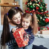 Happy little sister unpack gifts for Christmas. The concept of Christmas and New Year. royalty free stock images