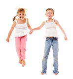 Happy little sisters. Two laughing sisters jumping isolated Stock Photos
