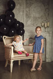 Happy little sisters with black balloons. Happy little sisters with black balloons in studio Stock Photos