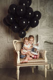 Happy little sisters with black balloons. Happy little sisters with black balloons in studio Stock Photo