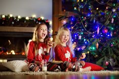 Happy little sisters having milk and cookies by a fireplace in a cozy dark living room on Christmas eve Stock Photography