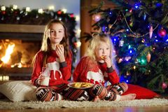Happy little sisters having milk and cookies by a fireplace in a cozy dark living room on Christmas eve Royalty Free Stock Images