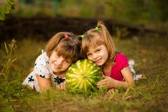 Happy little sisters lie on grass and hug very big watermelon in sunny day. Healthy concept. Happy little sisters lie on grass and hug very big watermelon in stock photo