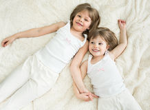 Happy little sisters lying top view. Happy little sisters lying on back top view royalty free stock photography