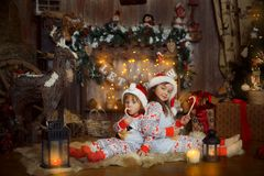 Little sisters in pajamas at Christmas Eve. Happy little sisters in pajamas playing near a fireplace at Christmas Eve Stock Photos