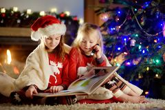Happy little sisters reading a story book together by a fireplace in a cozy dark living room on Christmas eve Royalty Free Stock Image