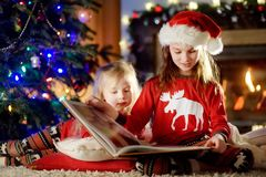 Happy little sisters reading a story book together by a fireplace in a cozy dark living room on Christmas eve Stock Photos