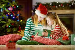 Happy little sisters wearing Christmas pajamas opening gift boxes by a fireplace in a cozy dark living room on Christmas eve. Royalty Free Stock Images