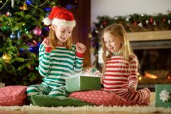Happy little sisters wearing Christmas pajamas opening gift boxes by a fireplace in a cozy dark living room on Christmas eve. royalty free stock photos