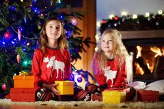 Happy little sisters wearing Christmas pajamas playing by a fireplace in a cozy dark living room on Christmas eve Stock Photography