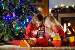 Happy little sisters wearing Christmas pajamas playing by a fireplace in a cozy dark living room on Christmas eve Stock Photo