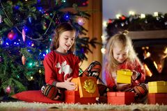 Happy little sisters wearing Christmas pajamas playing by a fireplace in a cozy dark living room on Christmas eve Royalty Free Stock Photography