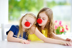Happy little sisters wearing red clown noses having fun together on sunny summer day at home Royalty Free Stock Images