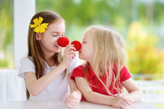 Happy little sisters wearing red clown noses having fun together on sunny summer day at home. Two kid playing together Royalty Free Stock Images