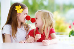 Happy little sisters wearing red clown noses having fun together on sunny summer day at home Stock Photo