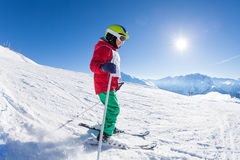 Happy little skier exercising on a mountain slope. Happy little skier learning and exercising on a mountain slope at sunny snowy day stock photography