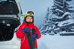 Happy little skier loading his skis in car trunk Stock Photos