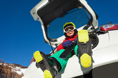 Happy little skier sitting in the car boot Royalty Free Stock Photos