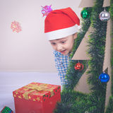 Happy little smiling boy with christmas gift box. Royalty Free Stock Images