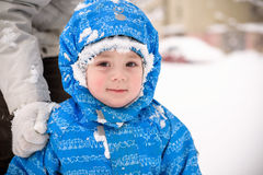 Happy little smiling boy outdoors in the snow in winter clothing. Kid has a frost on his face Royalty Free Stock Photos