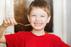 Happy little smiling young child hold spoon. Stock Photos