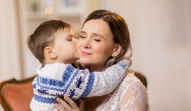 Happy little son kissing his mother. Family, expressions and love concept - happy little son kissing his mother Stock Image