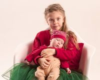 Happy little teen girl holding his newborn baby little sister. Family love. Happy little teen gir holding his newborn baby little sister at studio. Family love Royalty Free Stock Images