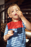 Happy little toddler boy eat berry Stock Images