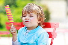 Happy little toddler boy eating colorful ice cream in summer Stock Photos