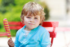 Happy little toddler boy eating colorful ice cream in summer Stock Photo