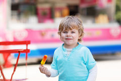 Happy little toddler boy eating colorful ice cream in summer Royalty Free Stock Images