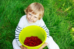 Happy little toddler boy with raspberries Stock Photography
