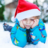 Happy little toddler boy waiting for Christmas santa hat Royalty Free Stock Photos