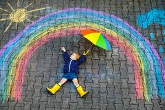 Free Happy Little Toddler Girl In Rubber Boots With Rainbow Sun And Clouds With Rain Painted With Colorful Chalks On Ground Stock Images - 173004054