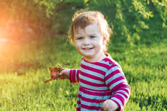 Happy little toddler girl walk outdoors on a sunny day holding leaves. Spring time, green grass. Royalty Free Stock Photo