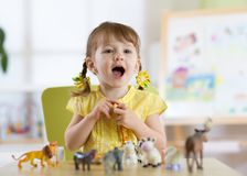 Happy little toddler plays animal toys at home or daycare centre Stock Photo