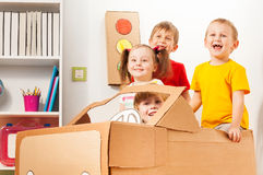 Happy little travelers driving cardboard car. Group of four happy 5 years old kids playing drivers with handmade cardboard car at the kindergarten Stock Images