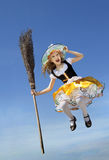 Happy Little Witch with a Broom flying high above the earth Stock Photography