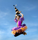Happy Little Witch Jumping at the Blue Sky Stock Image